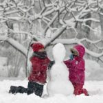 Children build  a snowman in a park in Bucharest, Romania, Monday, Dec. 29, 2014. Romania, especially the eastern part,  is affected by heavy snow falls and blizzards this year  that cause traffic disruptions but are enjoyed by children and mountain tourists. (AP Photo/Vadim Ghirda)